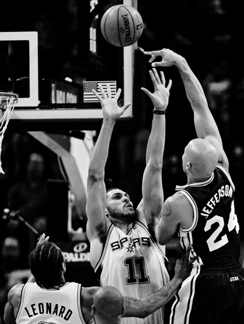 Utah Jazz forward Richard Jefferson, right, shoots over San Antonio Spurs forwards Jeff Ayres, center, and Kawhi Leonard during the second half of an NBA basketball game, Wednesday, Jan. 15, 2014, in San Antonio. San Antonio won 109-105. (AP Photo/Darren Abate)