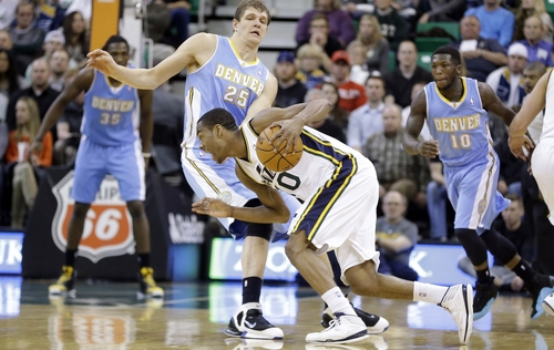 Utah Jazz's Alec Burks (10) drives against Denver Nuggets' Timofey Mozgov, of Russia, (25) while teammates Kenneth Faried (35) and Nate Robinson (10) look on in the second half during an NBA basketball game Monday, Jan. 13, 2014, in Salt Lake City. The Jazz won 118-103. (AP Photo/Rick Bowmer)