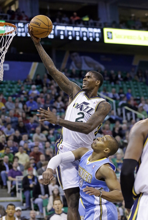 Utah Jazz's Marvin Williams (2) goes to the basket as Denver Nuggets' Randy Foye (4) defends in the first quarter during an NBA basketball game Monday, Jan. 13, 2014, in Salt Lake City. (AP Photo/Rick Bowmer)