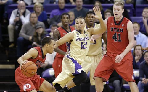 Washington's Andrew Andrews (12) defends Utah's Brandon Taylor, left, as Jeremy Olsen (41) looks on in the second half of an NCAA men's basketball game Wednesday, Jan. 8, 2014, in Seattle. Washington won 59-57. (AP Photo/Elaine Thompson)