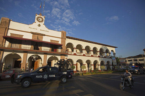 Federal police patrol outside City Hall in Apatzingan, Mexico, Wednesday, Jan. 15, 2014. Federal forces struggled to bring order to western Mexico as vigilantes battled a drug cartel. The unrest is in a region of Michoacan known as Tierra Caliente, a  farming area where vigilante groups have been trying to drive out the Knights Templar drug cartel. After a weekend of firefights, the government announced Monday that it would take on security duties in the area. (AP Photo/Eduardo Verdugo)