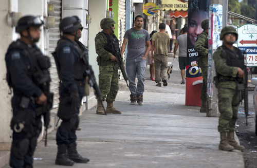 Federal police and soldiers stand guard in Apatzingan, Mexico, Wednesday, Jan. 15, 2014. Federal forces struggled to bring order to western Mexico as vigilantes battled a drug cartel. The unrest is in a region of Michoacan known as Tierra Caliente, a farming area where vigilante groups have been trying to drive out the Knights Templar drug cartel. After a weekend of firefights, the government announced Monday that it would take on security duties in the area. (AP Photo/Eduardo Verdugo)
