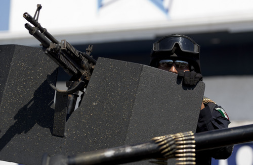 A federal police patrols the entrance to Apatzingan, Mexico, Tuesday, Jan. 14, 2014. Mexican soldiers and federal police kept a tense standoff with vigilantes Tuesday after a new government campaign to stop violence in the western Michoacan state turned deadly. A clash occurred as the government sent more troops to where the vigilantes have been fighting the Knights Templar cartel. Federal and state officials met late Tuesday with leaders of vigilante groups but failed to reach a disarmament agreement. (AP Photo/Eduardo Verdugo)