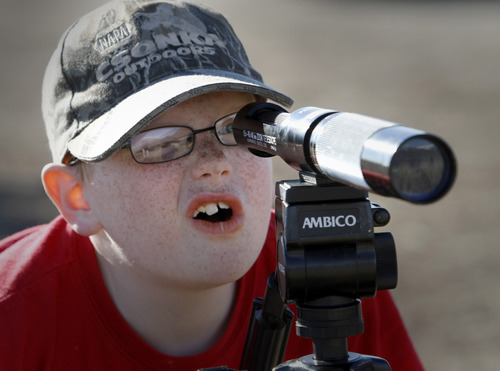 Rick Egan   |  The Salt Lake Tribune  Evan Putnam, 8, Salt Lake City, watches a Bald Eagle through a spotting scope at Farmington Bay Waterfowl Management Area, Saturday, February 12, 2011. Spotting scopes were provided to give bird lovers a closer look at the Eagles.