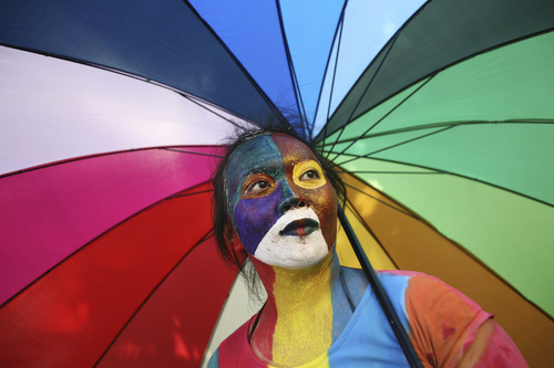 "Binsar Bakkara  |  Associated Press file photo An activist with multicolored paint on her face and matching umbrella participates in a protest demanding equality for LGBTIQ (Lesbian, gay, bisexual, transgender and questioning) people in Medan, North Sumatra, Indonesia in 2012. In heavily Muslim Indonesia, gay sex is not criminalized, and many young, urban Indonesians are relatively tolerant of homosexuality, but most citizens consider it unacceptable. ""Gay people are still living in fear,"" said King Oey, chairman of the country's main gay-rights group."