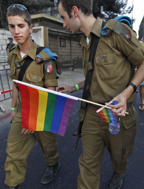 FILE - In this June 25, 2009 file photo, An Israeli soldier holds a rainbow flag as he and others march in a gay pride parade in Jerusalem. Public acceptance of gays in Israel and Lebanon is higher than the rest of the Middle East region, according to a Pew Research Center study released in 2013. (AP Photos/Tara Todras-Whitehill)