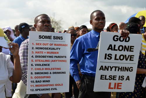 FILE - Jamaican churchgoers hold signs while attending an anti-gay rally in Kingston, Jamaica on Sunday, June 23, 2013. Several pastors in Jamaica led a revival meeting Sunday to oppose efforts to overturn the Caribbean country's anti-sodomy law and turn back what they see as increasing acceptance of homosexuality. (AP Photo/David McFadden)