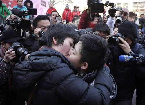 FILE - Photographers surround a lesbian couple as they kiss during an event to celebrate Valentine's Day organized near a shopping mall in Beijing on Monday, Feb. 14, 2011. Beijing's gay and lesbian community celebrated Valentine's Day by calling for greater gay rights in China on Monday in Beijing. Activists were supposed to take part in a kissing competition in the shopping mall in central Beijing, but the event was canceled after organizers said there was a lack of participants. (AP Photo/Andy Wong)