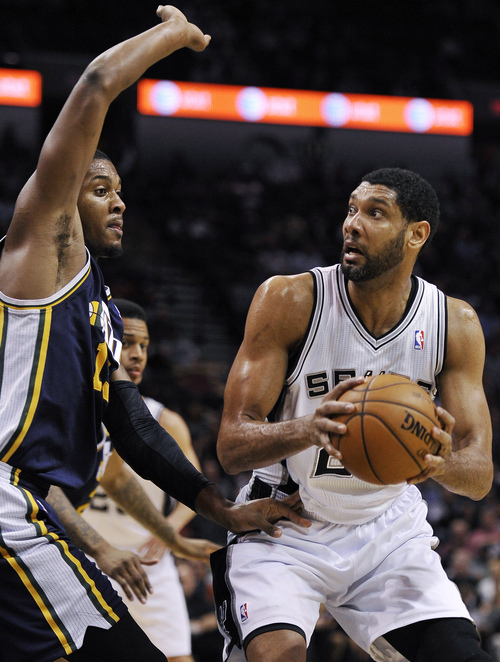 San Antonio Spurs forward Tim Duncan, right, looks to shoot against Utah Jazz forward Derrick Favors during the second half of an NBA basketball game, Wednesday, Jan. 15, 2014, in San Antonio. San Antonio won 109-105. (AP Photo/Darren Abate)
