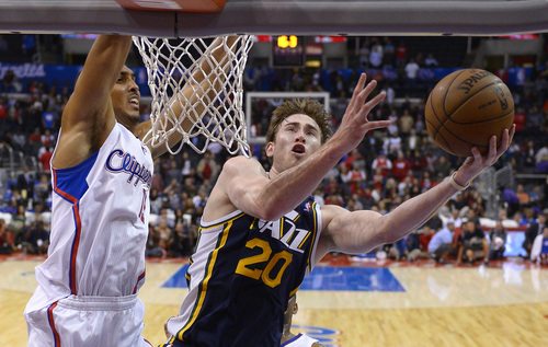 Utah Jazz small forward Gordon Hayward, right, puts up a shot as Los Angeles Clippers center Ryan Hollins defends during the second half of their NBA basketball game, Wednesday, Oct. 23, 2013, in Los Angeles. (AP Photo/Mark J. Terrill)