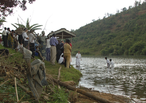 Mike Stack | Courtesy Newly baptized members of the LDS Church exit the water at Lake Muhazi, Rwanda, in 2010 while members and friends look on.