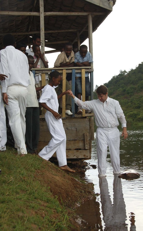 Mike Stack | Courtesy Eric Hyde,  president of the Kigali, Rwanda LDS Branch, helps a new convert into the water for baptism at Lake Muhazi.