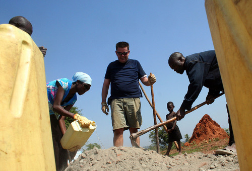 Jeremiah Stettler  |  The Salt Lake Tribune  SEEE Institute volunteer Tim Peters helps prepare cement for a new swing set outside the St. John Bosco Namwabula View Primary School in Katosi-Luganzi. It is being mixed Uganda-style, on the ground.