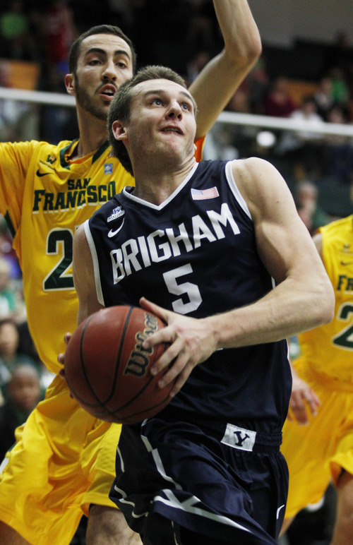 BYU's Kyle Collinsworth, front, drives for the basket past San Francisco's Mark Tollefsen, left, during the first half of an NCAA college basketball game, Thursday, Jan. 16, 2014, in San Francisco. (AP Photo/George Nikitin)