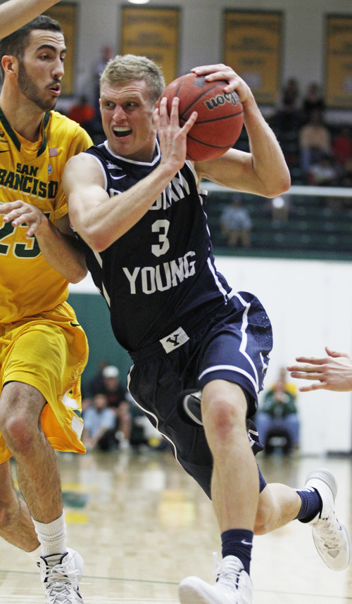 BYU's Tyler Haws, right, drives for the basket past San Francisco's Mark Tollefsen during the second half of an NCAA college basketball game, Thursday, Jan. 16, 2014, in San Francisco. BYU won 83-76. (AP Photo/George Nikitin)