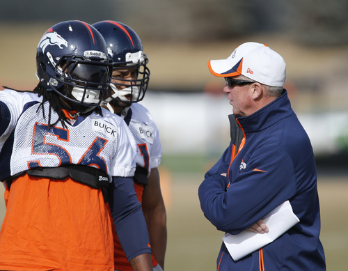 Denver Broncos head coach John Fox, right, talks to outside linebacker Nate Irving (56) and middle linebacker Paris Lenon (51) during NFL football practice at the team's training facility in Englewood, Colo., on Thursday, Jan. 16, 2014. The Broncos are scheduled to host the New England Patriots on Sunday in the AFC championship. (AP Photo/Ed Andrieski)