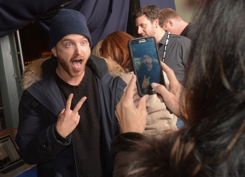 """Actor Aaron Paul poses for fans at the Chase Sapphire Preferred """"Hellion"""" premiere party during the Sundance Film Festival, on Friday, January 17, 2013 in Park City, Utah. (Photo by Evan Agostini/Invision for Chase Sapphire Preferred/AP Images)"""
