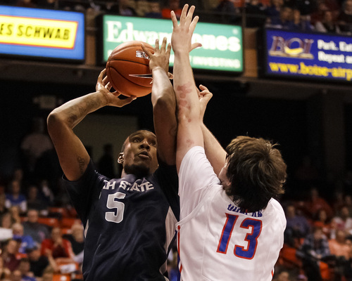 Utah State's Jarred Shaw (5) shoots over Boise State's Nick Duncan (13) during the second half of an NCAA college basketball game in Boise, Idaho, Saturday, Jan. 18, 2014. Boise State defeated Utah State 78-74. (AP Photo/Otto Kitsinger)