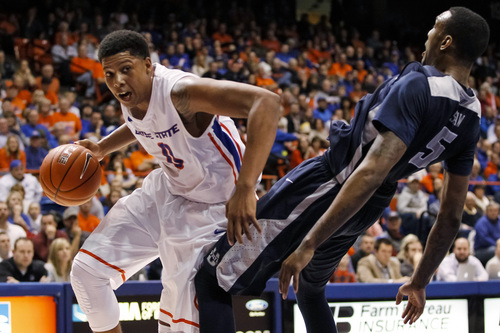 Boise State's Ryan Watkins (0) moves the ball around Utah State's Jarred Shaw (5) during the second half of an NCAA college basketball game in Boise, Idaho, on Saturday, Jan. 18, 2014. Boise State defeated Utah State 78-74. (AP Photo/Otto Kitsinger)