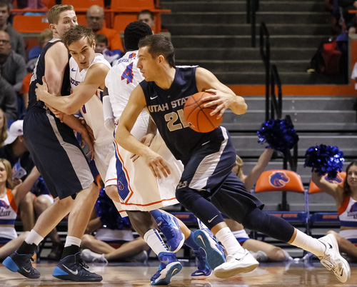 Utah State's Spencer Butterfield (21) moves the ball around Boise State's Thomas Bropleh (4) and Anthony Drmic, second from left, during the first half of an NCAA college basketball game in Boise, Idaho, Saturday, Jan. 18, 2014. (AP Photo/Otto Kitsinger)