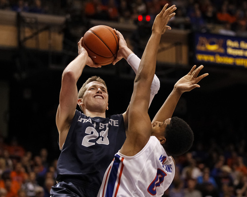 Utah State's Kyle Davis (23) shoots over Boise State's Ryan Watkins (0) during the first half of an NCAA college basketball game in Boise, Idaho, Saturday, Jan. 18, 2014. (AP Photo/Otto Kitsinger)