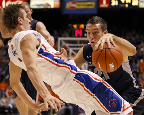 Utah State's Spencer Butterfield (21) moves the ball against Boise State's Anthony Drmic during the first half of an NCAA college basketball game in Boise, Idaho, Saturday, Jan. 18, 2014. (AP Photo/Otto Kitsinger)