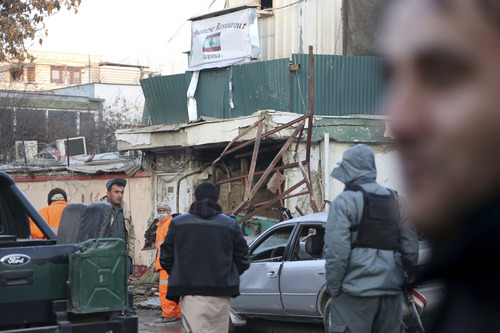Afghan security forces personnel investigate the Friday's suicide attack and shooting in Kabul, Afghanistan, Saturday, Jan. 18, 2014. A suicide bomber blew himself up outside a Kabul restaurant, seen in the background, filled with foreigners and affluent Afghans, while two gunmen snuck in through the back door and opened fire Friday in a brazen dinnertime attack that killed 16 people, officials said. (AP Photo/Rahmat Gul)