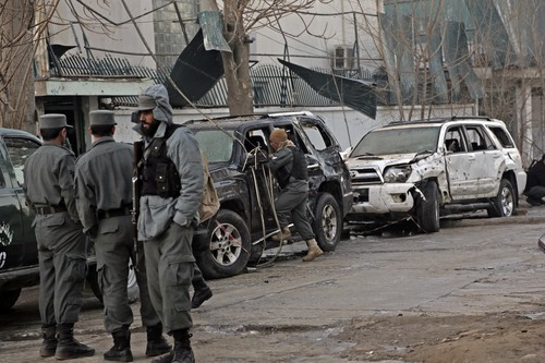 Afghan security forces personnel investigate the site of Friday's suicide attack and shooting, in Kabul, Afghanistan, Saturday, Jan. 18, 2014. A Taliban suicide bomber and two gunmen on Friday attacked a Lebanese restaurant that is popular with foreigners and affluent Afghans in Kabul, a brazen attack that left 16 dead, including foreigners dining inside and two other gunmen, officials said. (AP Photo/Rahmat Gul)