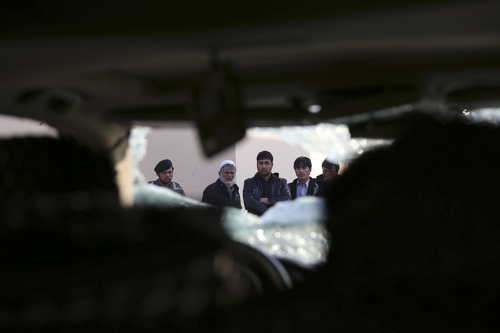 Afghan civilians watch a damaged vehicle following the Friday's suicide attack and shooting in Kabul, Afghanistan, Saturday, Jan. 18, 2014. A suicide bomber blew himself up outside a Kabul restaurant filled with foreigners and affluent Afghans, while two gunmen snuck in through the back door and opened fire Friday in a brazen dinnertime attack that killed 16 people, officials said. (AP Photo/Rahmat Gul)