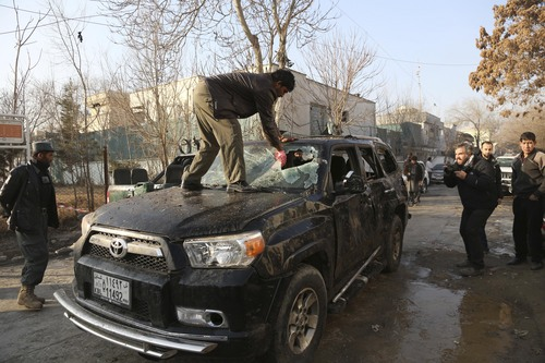 An Afghan driver removes a broken windshield of his car following the Friday's suicide attack and shooting in Kabul, Afghanistan, Saturday, Jan. 18, 2014. A Taliban suicide bomber and two gunmen on Friday attacked a Lebanese restaurant that is popular with foreigners and affluent Afghans in Kabul, a brazen attack that left 16 dead, including foreigners dining inside and two other gunmen, officials said. (AP Photo/Rahmat Gul)