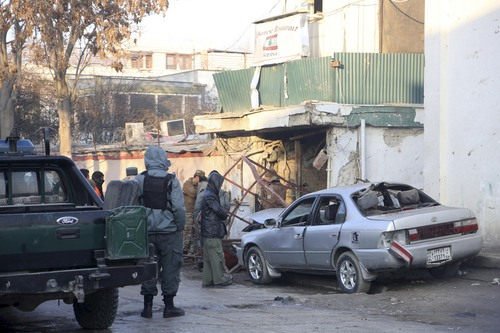 Afghan security forces personnel investigate at the site of the Friday's suicide attack and shooting, in Kabul, Afghanistan, Saturday, Jan. 18, 2014. A Taliban suicide bomber and two gunmen on Friday attacked a Lebanese restaurant that is popular with foreigners and affluent Afghans in Kabul, a brazen attack that left 16 dead, including foreigners dining inside and two other gunmen, officials said. (AP Photo/Rahmat Gul)