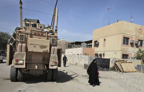 An Iraqi woman and child walk past a U.S. Army Mine Resistant Ambush Protected (MRAP) vehicle on a street in Baghdad, Iraq, Monday, March 8, 2010. The Utah Highway Patrol and Iron County Sheriff's Office recently acquired their own MRAPs. (AP Photo/Karim Kadim)