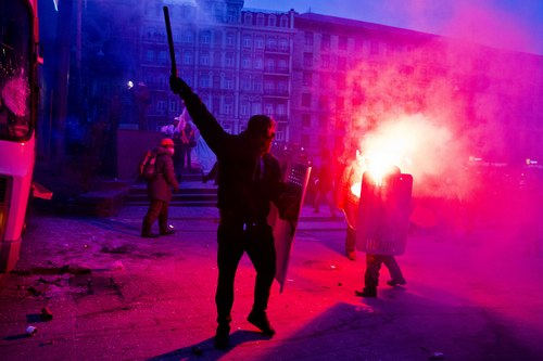 A protester swings a baton towards a burning police bus, in front of him, during clashes with police,  in central Kiev, Ukraine, Sunday, Jan. 19, 2014. Hundreds of protesters on Sunday clashed with riot police in the center of the Ukrainian capital, after the passage of harsh anti-protest legislation last week seen as part of attempts to quash anti-government demonstrations. The violent scenes further escalated this ex-Soviet republic?s political crisis and showed a rift among opposition leaders, one of whom fought bravely to stop the violence, while others condemned the events from afar. (AP Photo/Evgeny Feldman)