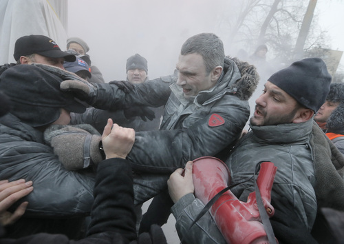 Opposition leader and former WBC heavyweight boxing champion Vitali Klitschko, center, is attacked and sprayed with a fire extinguisher as he tries to stop the clashes between police and protesters  in central Kiev, Ukraine, Sunday, Jan. 19, 2014. Hundreds of protesters on Sunday clashed with riot police in the center of the Ukrainian capital, after the passage of harsh anti-protest legislation last week seen as part of attempts to quash anti-government demonstrations. A group of radical activists began attacking riot police with sticks, trying to push their way toward the Ukrainian parliament building, which has been cordoned off by rows of police and buses. (AP Photo / Efrem Lukatsky)