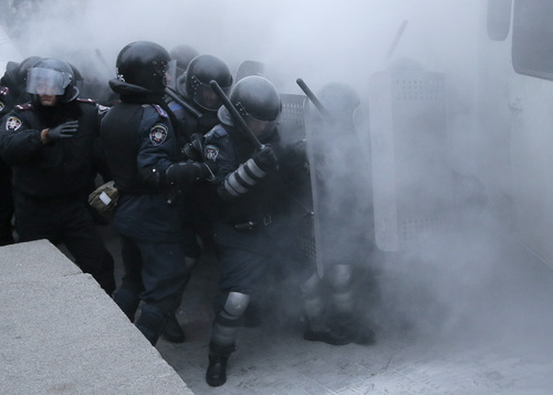 Riot police clash with protesters in central Kiev, Ukraine, Sunday, Jan. 19, 2014. Hundreds of protesters on Sunday clashed with riot police in the center of the Ukrainian capital, after the passage of harsh anti-protest legislation last week seen as part of attempts to quash anti-government demonstrations. A group of radical activists began attacking riot police with sticks, trying to push their way toward the Ukrainian parliament building, which has been cordoned off by rows of police and buses. (AP Photo / Efrem Lukatsky)