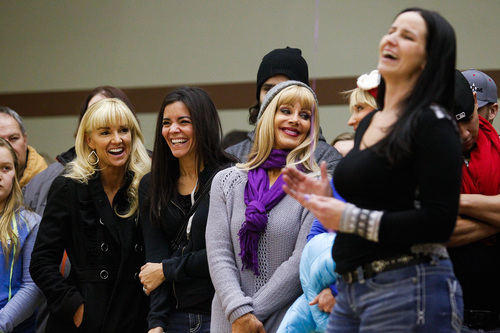 Robyn Maher, Nathalie Smith and Rona Hill smile as Stacy Archuleta, right, relays a funny story about Kelly Boren during a memorial service and candlelight vigil for the Boren family at the Gold's Gym in Spanish Fork, Utah on Saturday, Jan. 18, 2014. Authorities believe Joshua Boren, a police officer, shot and killed his wife, mother-in-law and two young children before turning the gun on himself.   (AP Photo/Daily Herald, Spencer Heaps)
