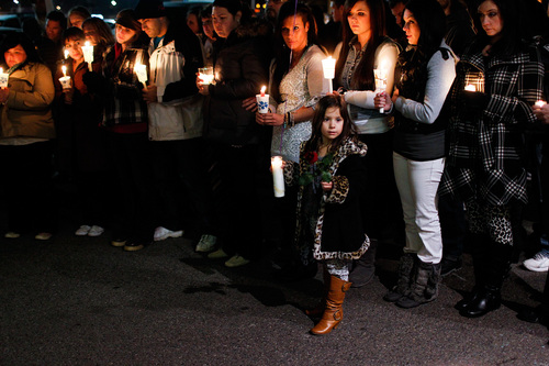 Rinnlie Whitting, 6, holds a candle and a flower during a memorial service and candlelight vigil for the Boren family at the Gold's Gym in Spanish Fork, Utah on Saturday, Jan. 18, 2014. Authorities believe Joshua Boren, a police officer, shot and killed his wife, mother-in-law and two young children before turning the gun on himself.   (AP Photo/Daily Herald, Spencer Heaps)