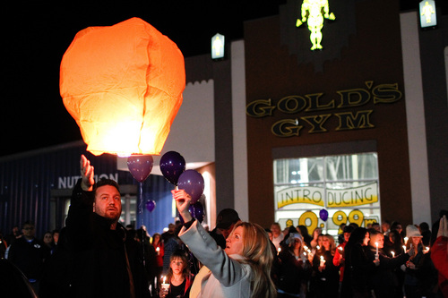 Shawn Andersen, left, and Kimberly King, center, release a lantern during a memorial service and candlelight vigil for the Boren family at the Gold's Gym in Spanish Fork, Utah on Saturday, Jan. 18, 2014. Authorities believe Joshua Boren, a police officer, shot and killed his wife, mother-in-law and two young children before turning the gun on himself.   (AP Photo/Daily Herald, Spencer Heaps)