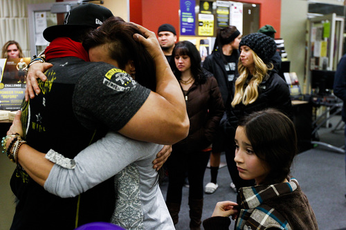 Telmo Torres, left, hugs RiRi Whiting, both friends of Kelly Boren, during a memorial service and candlelight vigil for the Boren family at the Gold's Gym in Spanish Fork, Utah on Saturday, Jan. 18, 2014. Authorities believe Joshua Boren, a police officer, shot and killed his wife, mother-in-law and two young children before turning the gun on himself.    (AP Photo/Daily Herald, Spencer Heaps)
