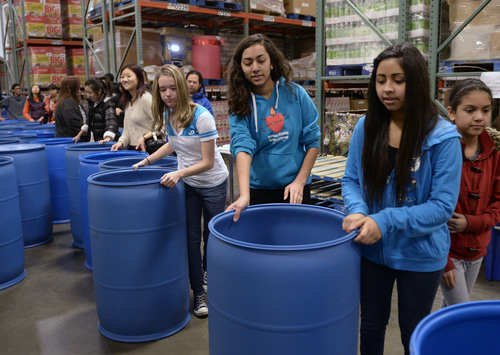 Al Hartmann  |  The Salt Lake Tribune Student volunteers from Youth City, Americorps, and Juan Diego High School gathered at the Utah Food Bank to clean and organize food barrels to celebrate Martin Luther King Day.  They form a line pushing hundred of the cleaned barrels through the warehouse and up a set of stairs for storage. The students were joined by other private individuals and corporate groups to prepare food boxes and deliver them to elderly and others with food needs.