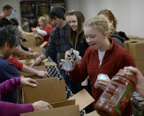 Al Hartmann  |  The Salt Lake Tribune Volunteers from youth groups, private individuals and corporate groups gathered at the Utah Food Bank for Martin Luther King Day to clean food barrels and prepare food boxes for delivery to elderly and others with food needs.