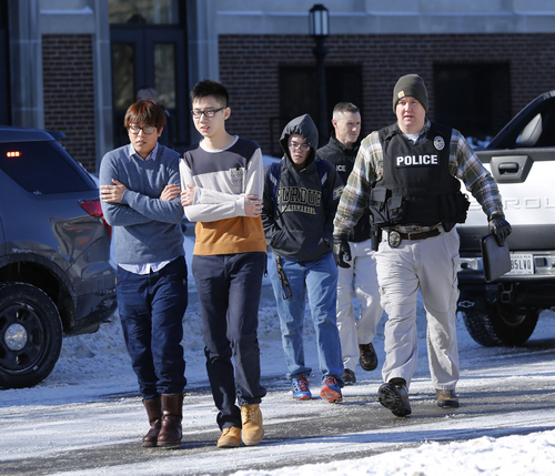 Police evacuate students from the Electrical Engineering building after shots were fired on Tuesday, Jan. 21, 2014, on the campus of Purdue University in West Lafayette, Ind.  Officials at Purdue University say one person has been killed in a shooting at the campus classroom building. Purdue Provost Tim Sands says he didn't immediately know the identity of the person killed or the person's connection to the university. Campus police chief John Cox says the suspect is in custody after surrendering outside the Electrical Engineering Building following the shooting.   (AP Photo/Journal & Courier, John Terhune)   MANDATORY CREDIT