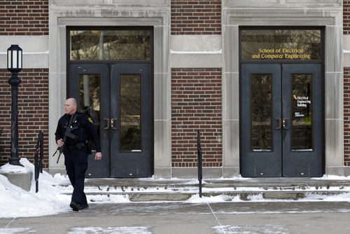 A police officer walks out of the Electrical Engineering Building on the campus of Purdue University in West Lafayette, Ind., Tuesday, Jan. 21, 2014 where  one person was killed inside a classroom by a gunman who surrendered to a police officer within minutes of the attack, officials said.. (AP Photo/Michael Conroy)