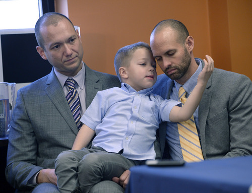 Al Hartmann  |  The Salt Lake Tribune Plaintiffs Matthew Barraza, left, and Tony Milner, who are legally married, listen to the announcement with their son Jesse, regarding the ACLU of Utah filing a lawsuit Tuesday Jan. 21, 2014, in Salt Lake City over Utah's refusal to recognize valid same-sex marriages that occurred before the U.S. Supreme Court issued a stay.