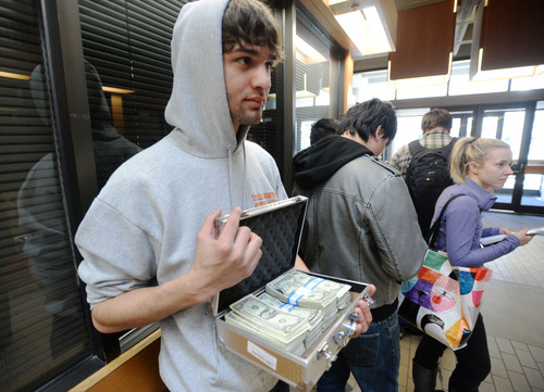 Steve Griffin  |  The Salt Lake Tribune University of Utah student Luq Mughal holds a briefcase full of $1 bills as he waits in a long line to pay his tuition at the Student Services Building on the University of Utah campus in Salt Lake City Tuesday. Mughal paid  his tuition in $1 bills to protest the high cost of tuition.