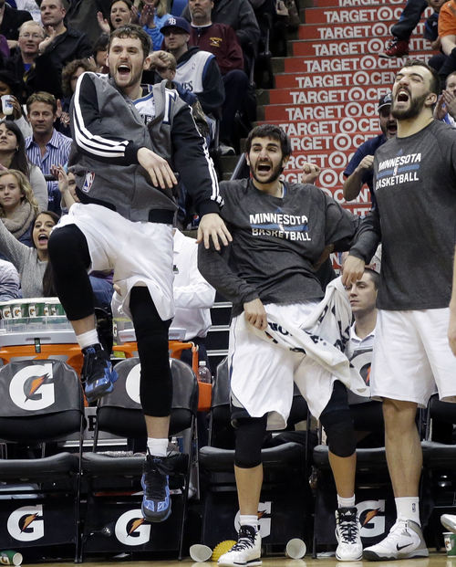 Minnesota Timberwolves' Kevin Love, left, Ricky Rubio, center, and Nikola Pekovic, right, celebrate a dunk by Gorgui Dieng during the second half of an NBA basketball game against the Utah Jazz, Saturday, Jan. 18, 2014, in Minneapolis. The Timberwolves won 98-72. (AP Photo/Jim Mone)