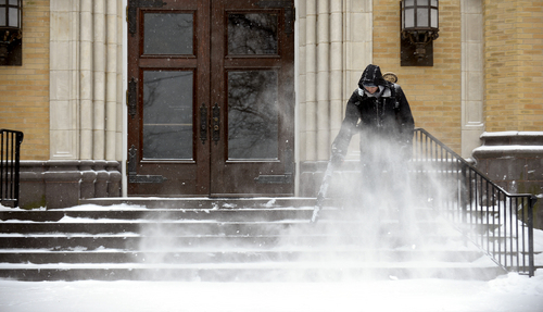 Dan Schramm, a senior at Lebanon Valley College, uses a backpack blower to clear snow off the steps of the humanities building on Tuesday, Jan. 21, 2014, in Annville Township, Pa. The National Weather Service predicts the storm could drop 8 to 12 inches of snow followed by bitterly cold temperatures. (AP Photo/Lebanon Daily News, Jeremy Long)  THE PATRIOT-NEWS OUT