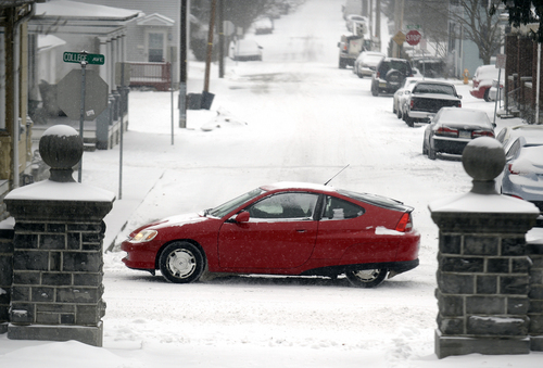 A car travels in the snow on Tuesday, Jan. 21, 2014, in Annville Township, Pa. The National Weather Service predicts the storm could drop 8 to 12 inches of snow followed by bitterly cold temperatures. (AP Photo/Lebanon Daily News, Jeremy Long)  THE PATRIOT-NEWS OUT