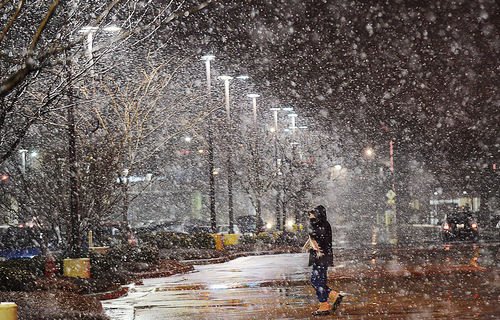 A pedestrian leaves the Target store off Durham Chapel Hill Boulevard, and walks toward the parking, during a snowy evening, Tuesday, Jan. 21, 2014 in Durham, N.C. (AP Photo/The Herald-Sun, Bernard Thomas)