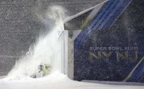 Workers shovel snow near a tent which will be used as an access point into Super Bowl XLVIII as crews prepare MetLife Stadium during a snow storm, Tuesday, Jan. 21, 2014, in East Rutherford, N.J. The NFL football title game, held Feb. 2, will be the first Super Bowl held outdoors in a city where it snows. (AP Photo/Julio Cortez)